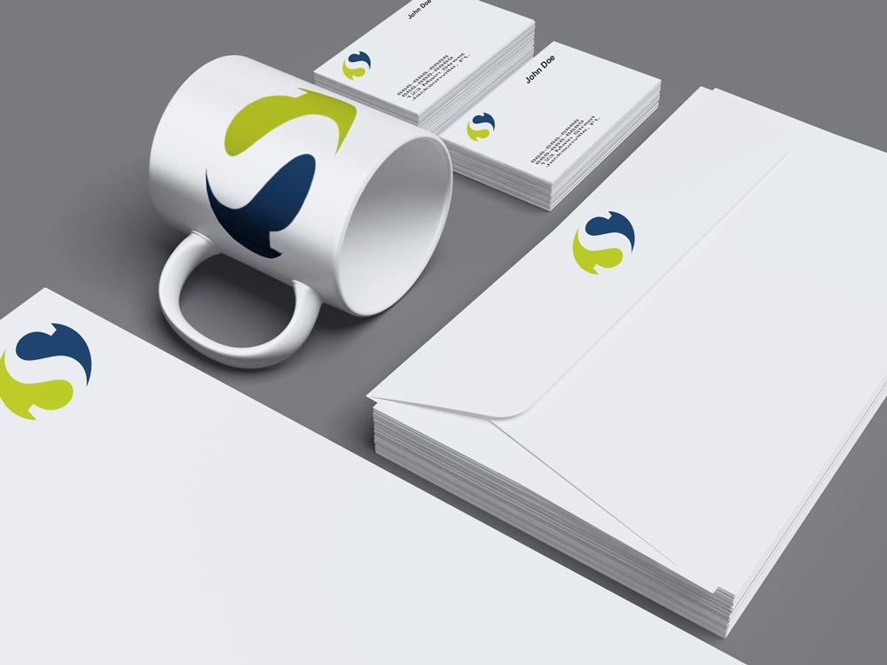 Photo of coffee mug, folder and business cards with a logo on them.